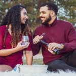 Couple holding wine bottle and wine glass smiling