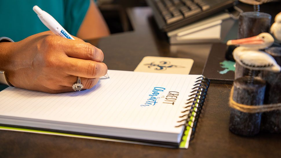 Pelican team member writing Credit vs. Character on paper with a Pelican pen