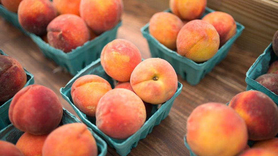 Peaches separated by baskets on a table.